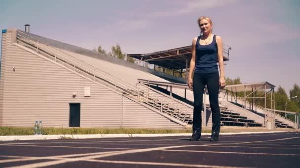 Mladá dívka, sportovní fyzičtina na stadionu. Jde na začátek řádku, dostane se do nízkého startu a začne se stisknout.