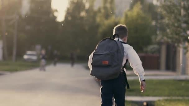 Cu, követés, lassú mozgás, vissza nézet shot: diák után iskolai órák runnning haza.
