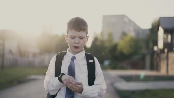 Cu, követés: portré iskolás, a hátizsákot háta mögött, az iskolai egyenruhát. Ő számít az ujjain.