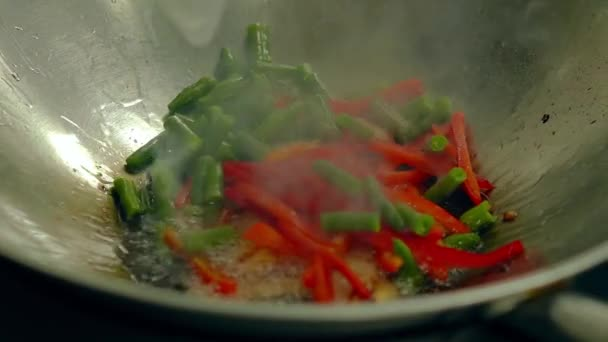 Close up slow motion shot Cooking fresh vegetables on hot frying pan, add them to pre-toasted potatoes.