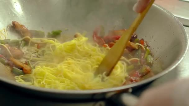CU, Slow motion: Cook prepares pasta in frying pan, in oil, with fresh vegetables
