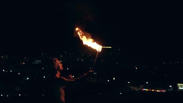 Fiatal szőke férfi lélegzik ki nagy patak a tűz fáklyával a fekete háttér. Lassított lövés.
