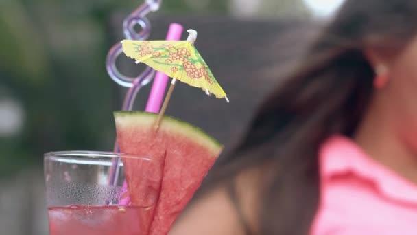 Großes Glas mit Wassermelone steht vor junger Frau