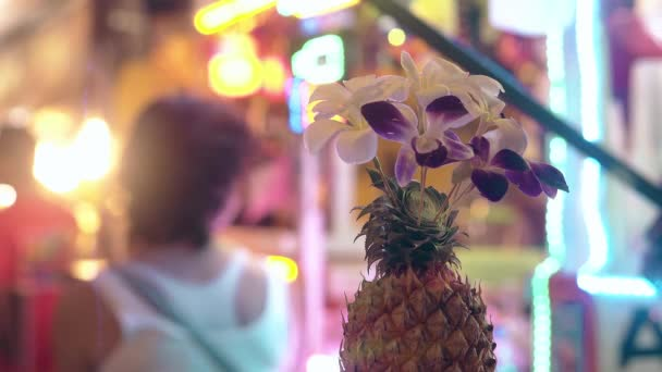 pineapple with orchids on blurred background with woman