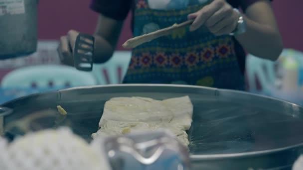 zkušený muž s hodinkou na levé straně přidává máslo na pečivo