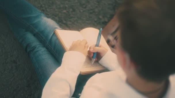 fiatal srác fehér ing és kék farmer rajzol a könyv lap