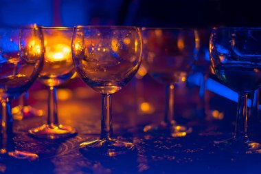glasses for alcoholic drinks in the rays of multi-colored light and lazar on a dark background