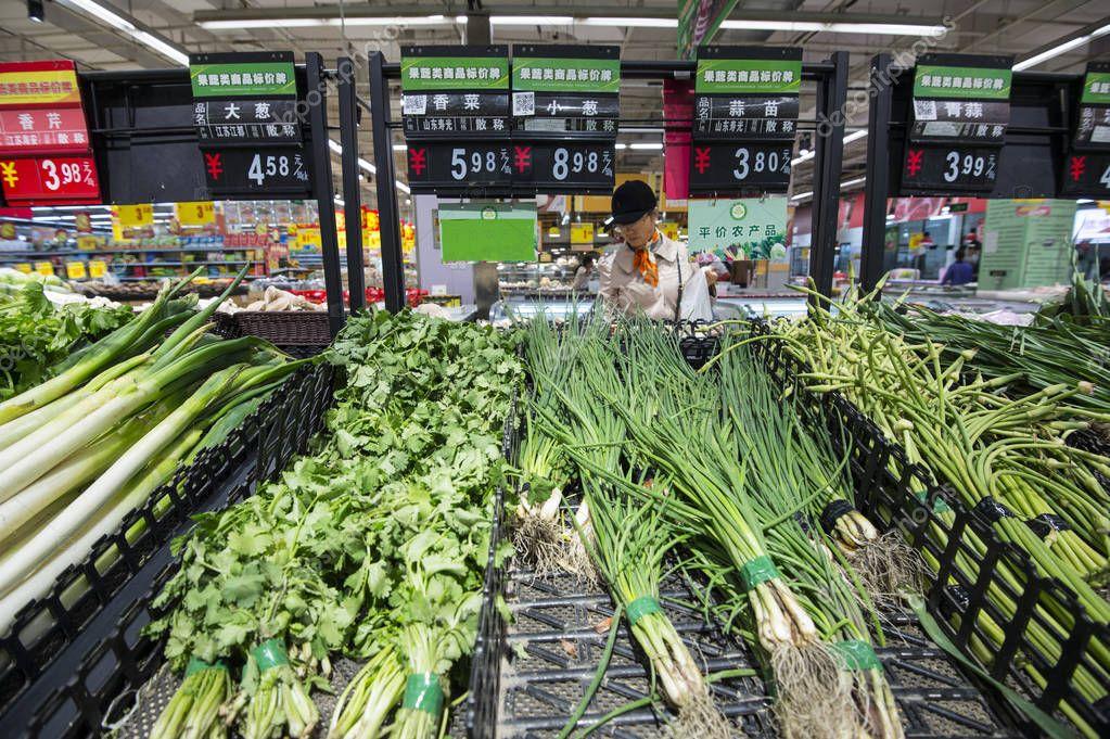 A customer shops for vegetables at a supermarket in Hai'an city, Nantong city, east China's Jiangsu province, 9 November 2018