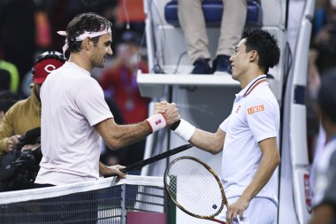 Roger Federer of Switzerland, left, interacts with Kei Nishikori of Japan in their quarterfinal match of the men's singles during the Rolex Shanghai Masters 2018 tennis tournament in Shanghai, China, 12 October 2018.