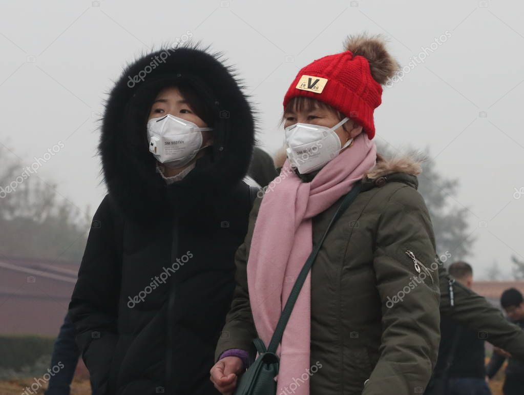 Tourists wearing face masks against air pollution visit the Tiananmen Square in heavy smog in Beijing, China, 2 December 2018
