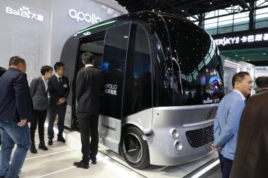 Visitors look at the Apolong, China's first self-driving microcirculation bus jointly developed by Baidu and the Chinese commercial vehicle maker King Long, at the Light of Internet Expo during the 5th World Internet Conference (WIC), also kn