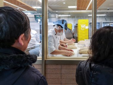 Customers watch chefs making breads at the Wu Pao Chun Bakery scheduled to officially open next week on Huaihai Road in Shanghai, China, 11 December 2018