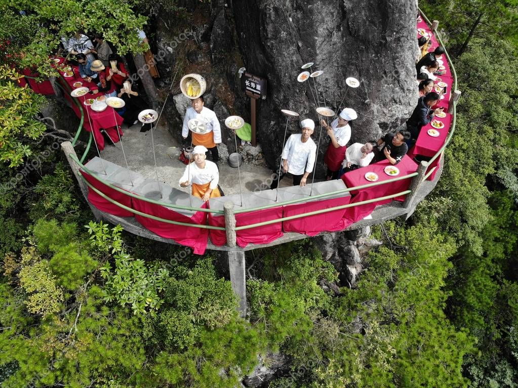 Chinese chefs perform disc-spinning on a terrifying cliff-side walkway at a cliff restaurant on the Longquan Mountain in Lishui city, east China's Zhejiang province, 27 September 2018