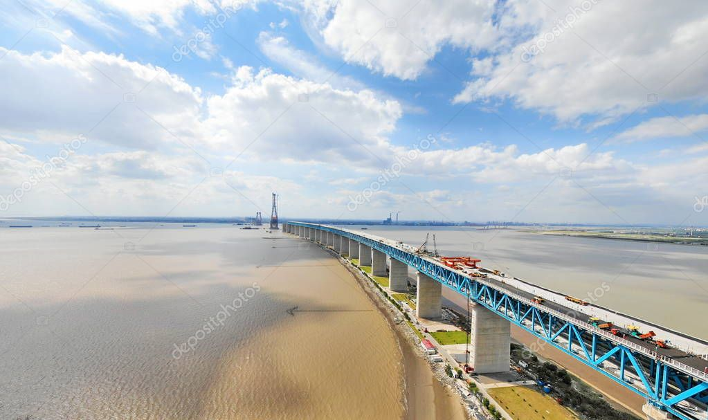 Chinese workers operate road paver to paint bitumen on the world's longest cable-stayed bridge, the Hutong (Shanghai-Nantong) Yangtze River Bridge, on the Yangtze River in east China's Jiangsu province, 25 September 2018.