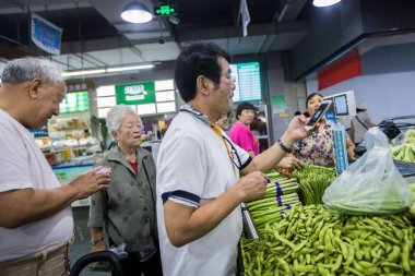 A citizen uses his smartphone to scan the QR code of WeChat Payment of the messaging app Weixin, or WeChat, of Tencent to pay for vegetables at a market in Hangzhou city, east China's Zhejiang province, 4 June 2018