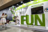 A girl makes live streaming webcast as she walks past the stand of Chinese online video site iQiyi during the 14th China International Cartoon  Game Expo, also known as CCG Expo 2018, in Shanghai, China, 6 July 201