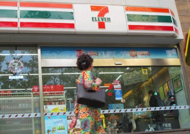A pedestrian walks past a 7-Eleven convenience store in Shanghai, China, 22 September 2017