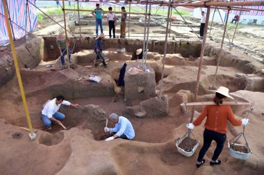 Chinese workers investigate the excavation site of the Shimen Pagoda ruins to unearth relics, which are mainly from the Shang Dynasty (c.1600 BC-1046 BC), along the Lishui River in Chujiang town, Shimen county, Changde city, central China's Hunan pro