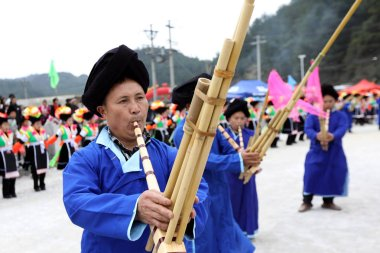 Chinese people of Miao ethnic minority play the traditonal wind instrument called