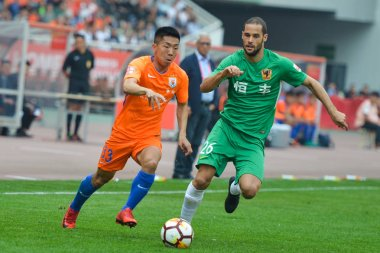 Spanish soccer player Mario Suarez, right, of Guizhou Hengfeng challenges a player of Shandong Luneng Taishan in their fourth round match during the 2018 Chinese Football Association Super League (CSL) in Ji'nan city, east China's Shandong province,