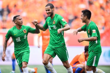 Spanish soccer player Mario Suarez, center, of Guizhou Hengfeng celebrates with his teammates after scoring against Shandong Luneng Taishan in their fourth round match during the 2018 Chinese Football Association Super League (CSL) in Ji'nan city, ea