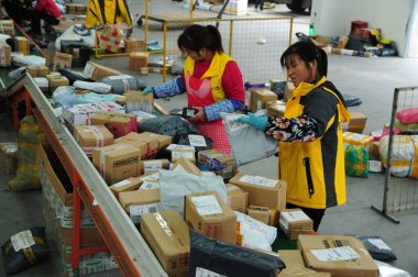 Chinese workers sort out piles of parcels, most of which are from Singles Day online shopping, at a distribution center in Suzhou city, east China's Jiangsu province, 14 November 2017
