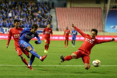 Paraguayan soccer player Oscar Romero, left, of Shanghai Greenland Shenhua shoots against players of Changchun Yatai in their 1st round match during the 2018 Chinese Football Association Super League (CSL) in Shanghai, China, 2 March 2018.
