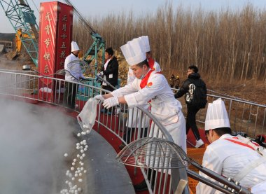 Chinese chefs cook glutinous rice balls, also known as Yuanxiao or Yuan Xiao, in a huge pot with a diameter of 9.9 meters during a lantern fair to celebrate the Lantern Festival on Kuanhouli Street in Ji'nan city, east China's Shandong province, 2 Ma