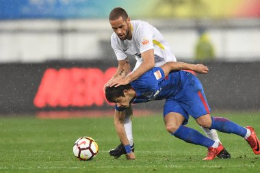 Spanish soccer player Mario Suarez, top, of Guizhou Hengfeng kicks the ball to make a pass against Paraguayan soccer player Oscar Romero of Shanghai Greenland Shenhua in their third round match during the 2018 Chinese Football Association Super Leagu