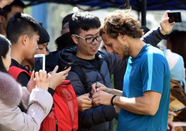Uruguayan football player Diego Forlan, right, signs autographs for fans during his first training session at the Kitchee training centre after joining the Kitchee SC of the Hong Kong Premier League in Hong Kong, China, 13 January 2018.