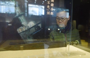 A visitor looks at a bronze sword of King Goujian of Yue (reigned 496 BCE - 465 BCE) inlaid with gold and silver on display at Xilin Yingshe Auction's autumn auction in Hangzhou city, east China's Zhejiang province, 20 December 2017