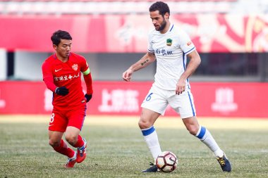 Spanish football player Mario Suarez, right, of Guizhou Hengfeng Zhicheng dribbles against a player of Yanbian Funde in the 30th round match during the 2017 Chinese Football Association Super League (CSL) in Yanji city, northeast China's Jilin provin