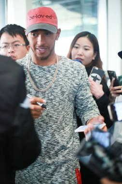 British F1 driver Lewis Hamilton of Mercedes signs autographs for fans at the Beijing Capital International Airport in Beijing, China, 2 April 2017.