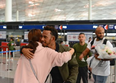 British F1 driver Lewis Hamilton of Mercedes, second left, hugs a fan as he arrives at the Beijing Capital International Airport in Beijing, China, 3 April 2017.