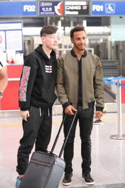 British F1 driver Lewis Hamilton of Mercedes, right, poses with a fan for a photo as he arrives at the Beijing Capital International Airport in Beijing, China, 3 April 2017.