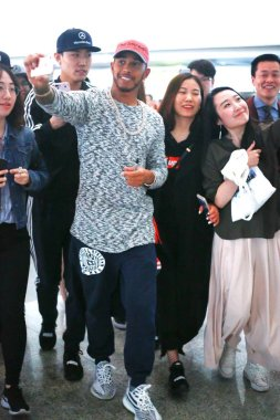 British F1 driver Lewis Hamilton of Mercedes takes selfies with Chinese fans at the Beijing Capital International Airport in Beijing, China, 2 April 2017.