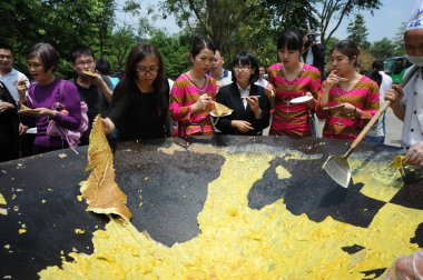 Visitors share pancakes on a pan 3 meters in diameter during a gourmet festival in Fogang county, south China's Guangdong province, 23 April 2017