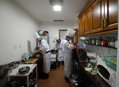 Chefs from a private kitchen platform cook in a customer's kitchen in Chengdu city, southwest China's Sichuan province, 14 May 2017