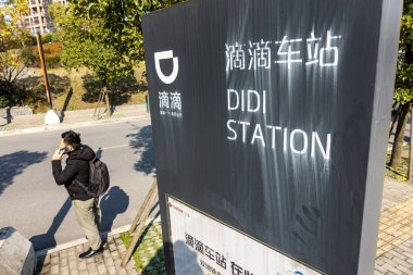 --FILE--A pedestrian walks past a Didi Station of of taxi-hailing and car service Didi Chuxing in Shanghai, China, 29 December 2018