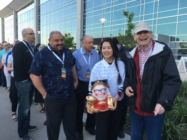 A Chinese immigrant holds a customized 3D printing sculpture of traditional Chinese Caishen, also known as God of Wealth, featuring a face similar to American business magnate Warren Buffett as he attends the annual Berkshire Hathaway shareholders me