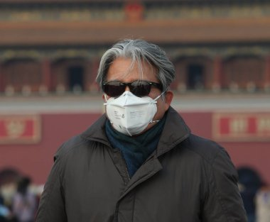 A tourist wearing a face mask visits Tiananmen Square in smog in Beijing, China, 15 January 2017