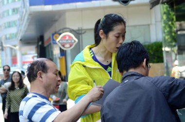 Chinese volleyball star Zhu Ting, center, is requested by fans to sign autographs when she and teammates of the Henan women's volleyball team walk on the street as they go out for a training session for the National Games 2017 in Shanghai, China, 17