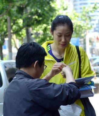 Chinese volleyball star Zhu Ting, back, is requested by a fan to sign autographs when she and teammates of the Henan women's volleyball team walk on the street as they go out for a training session for the National Games 2017 in Shanghai, China, 17 M