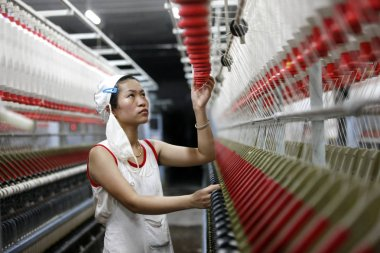 A female Chinese worker handles production of yarn to be exported to Southeast Asia on a spinning machine at a textile factory in Huaibei city, east China's Anhui province, 28 August 2015