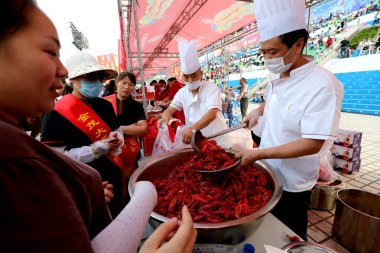 Chinese chefs serve residents and tourists during a crayfish banquet in Xuyi county, Huaian city, east China's Jiangsu province, 13 June 2017