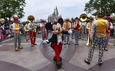An entertainer dressed in a Mickey Mouse costume performs during a parade at the first anniversary celebration ceremony in the Shanghai Disneyland at the Shanghai Disney Resort in Pudong, Shanghai, China, 16 June 2017
