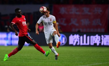 Cameroonian football player Olivier Boumal, left, of Liaoning Whowin challenges a player of Changchun Yatai in their 19th round match during the 2017 Chinese Football Association Super League (CSL) in Shenyang city, northeast China's Liaoning provinc