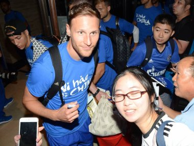 German football player Benedikt Howedes of FC Schalke 04, left, poses for selfies with a fan after arriving at a hotel in Shanghai, China, 17 July 2017.