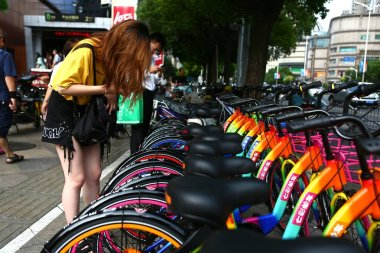 Local residents use their smartphone to scan QR codes on seven-colored shared bicycles of Chinese bike-sharing service 7sebike on a street in Shanghai, China, 20 June 2017