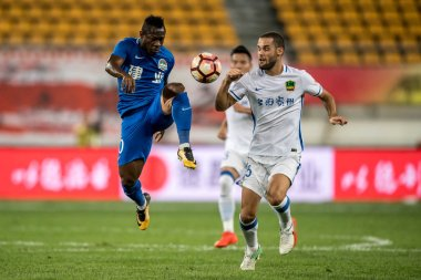 Spanish football player Mario Suarez, right, of Guizhou Hengfeng Zhicheng, challenges Cameroonian football player Christian Bassogog of Henan Jianye in their 25th round match during the 2017 Chinese Football Association Super League (CSL) in Guiyang